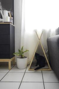 Tipi pour chat posé en bout de canapé avec un chat noir à l'intérieur