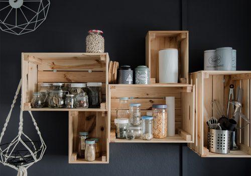 Cagettes en bois clair sur un mur gris anthracite, décoration écoresponsable et aménagement d'une cuisine
